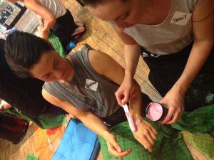 Jenny von I love Spa reicht Sandra von Healing Yoga Berlin etwas von der Fair Trade Lotion